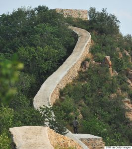 "This picture taken on September 21, 2016 shows a villager standing on a paved-over section of the Great Wall of China at Suizhong, in China's northeast Liaoning province. Chinese social media users were in an uproar on September 23 over restoration of a 700-year-old section of the Great Wall that has been covered in concrete, turning it into a smooth, flat-topped path. Known as one of the most beautiful portions of the ""wild"", unrestored wall, the eight-kilometre (five-mile) Xiaohekou stretch in northeast Liaoning province was built in 1381 during the Ming Dynasty. / AFP / STR / China OUT (Photo credit should read STR/AFP/Getty Images)"